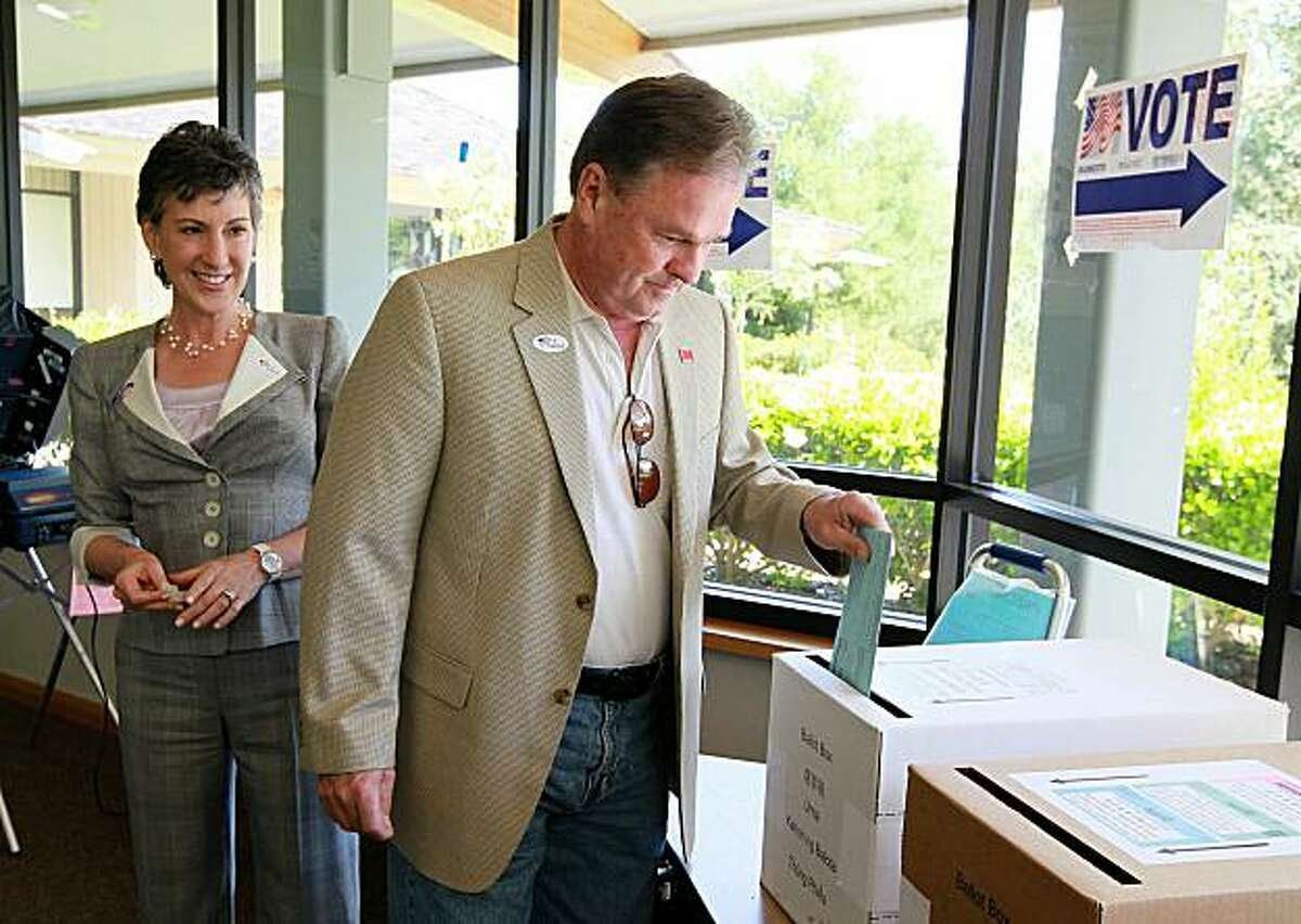 LOS ALTOS HILLS, CA - JUNE 08: Republican candidate for U.S. Senate and former HP CEO Carly Fiorina (L) looks on as her husband Frank Fiorina (R) casts his ballot at a polling place June 8, 2010 in Los Altos Hills, California. Fiorina cast her ballot forthe California primary election as she hopes to win the republican primary which she is in a tight race with former California congressman Tom Campbell.