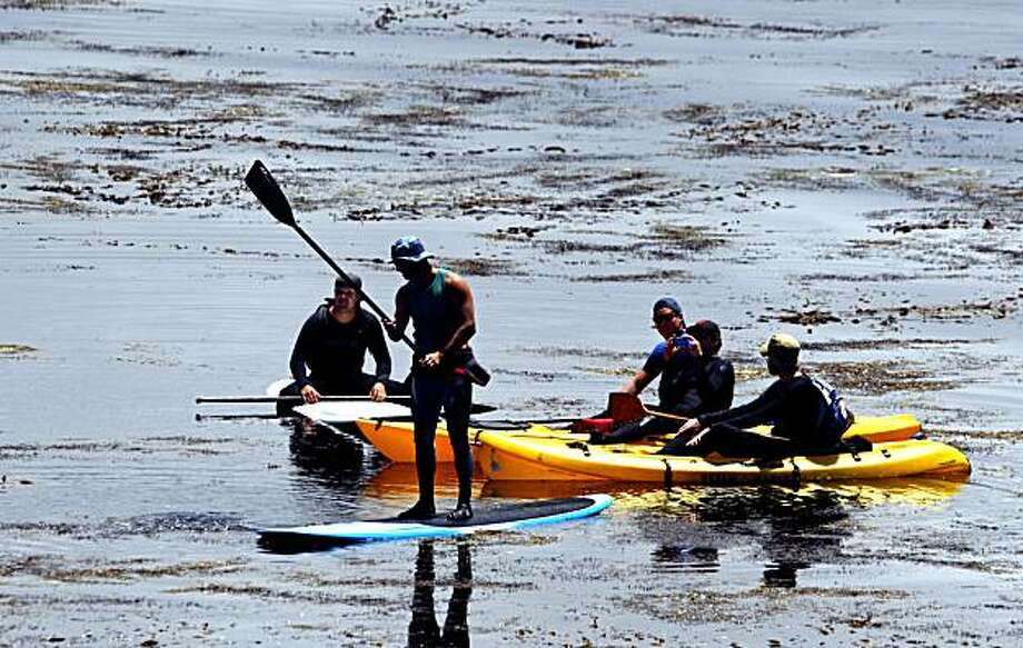 Paddle Boarders and kayakers watch 3rd round action off the 18th green during the 110th US Open golf tournament at Pebble Beach Still Water Cove Saturday June 19, 2010 Photo: Lance Iversen, The Chronicle