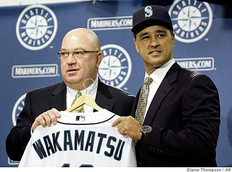 New Seattle Mariners manager Don Wakamatsu, right, poses with a new jersey and with general manager Jack Zduriencik at a news conference announcing his hiring Wednesday, Nov. 19, 2008, in Seattle.  Wakamatsu became the first Asian-American manager in major league baseball history when he was hired Wednesday by the Seattle Mariners. The Mariners' 14th manager, Wakamatsu was bench coach for the Oakland Athletics last season. Before that he spent five years with the Texas Rangers. (AP Photo/Elaine Thompson) Photo: Elaine Thompson, AP