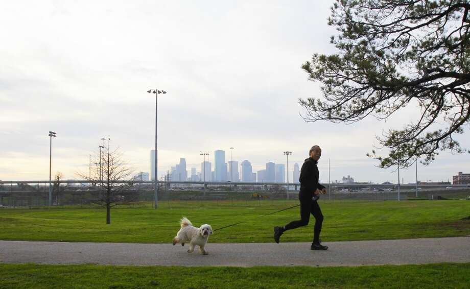 Cliff Ando runs with his dog, Maya, through Stude Park. He said the morning temperature is good for run ing, but he is welcoming the rain projected in the forecast. (Cody Duty/Chronicle)