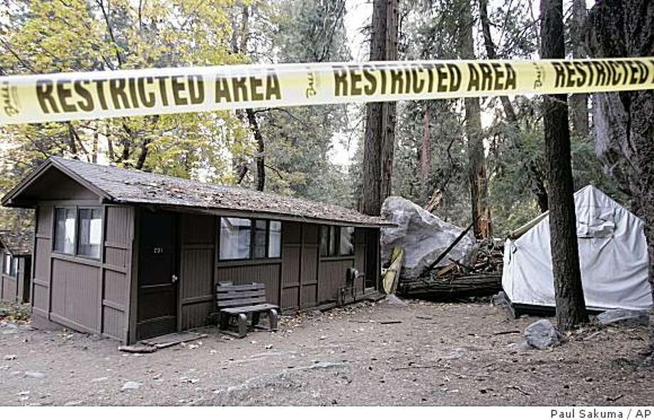 Restriction tape blocks an area at Curry Village in Yosemite National Park, Calif., after a boulder fell during a rock slide, Monday, Oct. 20, 2008. Falling rocks at one of America's most popular parks, Yosemite, have led to lawsuits and scientific debate over whether construction in the park has increased the danger and contributed to the deaths. Since 1999, 20 of the structures at Curry Village have been directly hit by boulders and many more damaged by flying rocks. (AP Photo/Paul Sakuma) Photo: Paul Sakuma, AP