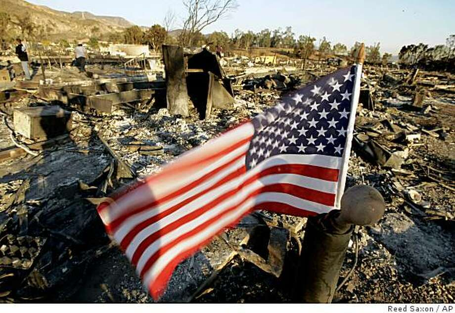 A small American flag flies atop a burned lamppost at what was the home of Teri Wagoner as residents of the Oakridge Mobile Home Park return to their homes in the Sylmar area of Los Angeles  Tuesday, Nov. 18, 2008, after wildfires destroyed hundreds of homes here Nov. 15.  (AP Photo/Reed Saxon) Photo: Reed Saxon, AP