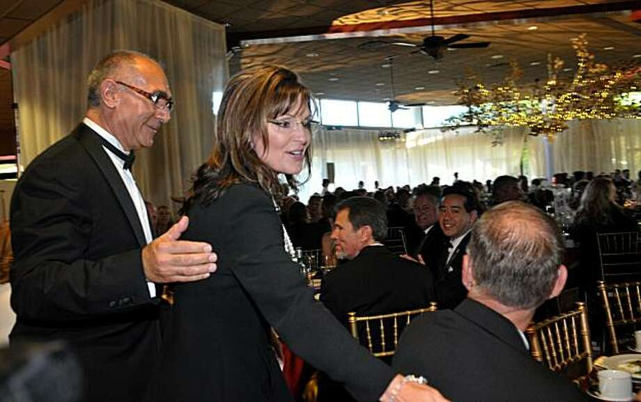 Sarah Palin, left, is escorted by California State University, Stanislaus' Hamid Shirvani, as they enter and begin to greet the attendees in the main dining room at California State University, Stanislaus in Turlock, California, Friday, June 25, 2010. The rormer vice-presidential candidate and governor of Alaska was the guest speaker at the 50th Anniversary of CSU, Stanislaus Gala. (Debbie Noda/Modesto Bee/MCT) Photo: Debbie Noda, MCT