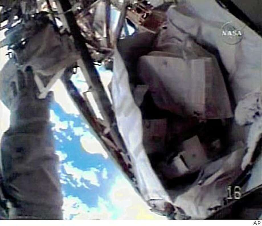 In this image from NASA TV, the hand of astronaut Heidemarie Stefanyshyn-Piper is seen at left, through her helmet camera, reaching for a tool kit bag that was lost from her grasp during a procedure during a space walk outside the International Space Station, Tuesday, Nov. 18, 2008. (AP Photo/NASA TV) Photo: AP