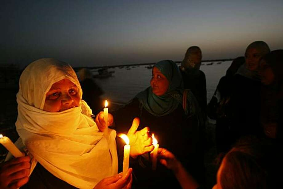 Palestinian women hold candles during a rally to support two Lebanese ships planning to sail from Lebanon to the Gaza Strip on a trip that aims to break Israel's blockade and to deliver aid, on June 21, 2010, in Gaza City's port. Photo: Mohammed Abed, AFP/Getty Images