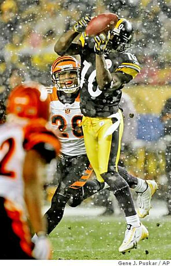Pittsburgh Steelers receiver Santonio Holmes (10) catches a pass as Cincinnati Bengals cornerback Leon Hall (29) moves in to make the tackle after a 22-yard gain during the second quarter of an  NFL football game, Thursday, Nov. 20, 2008, in Pittsburgh. (AP Photo/Gene J. Puskar) Photo: Gene J. Puskar, AP
