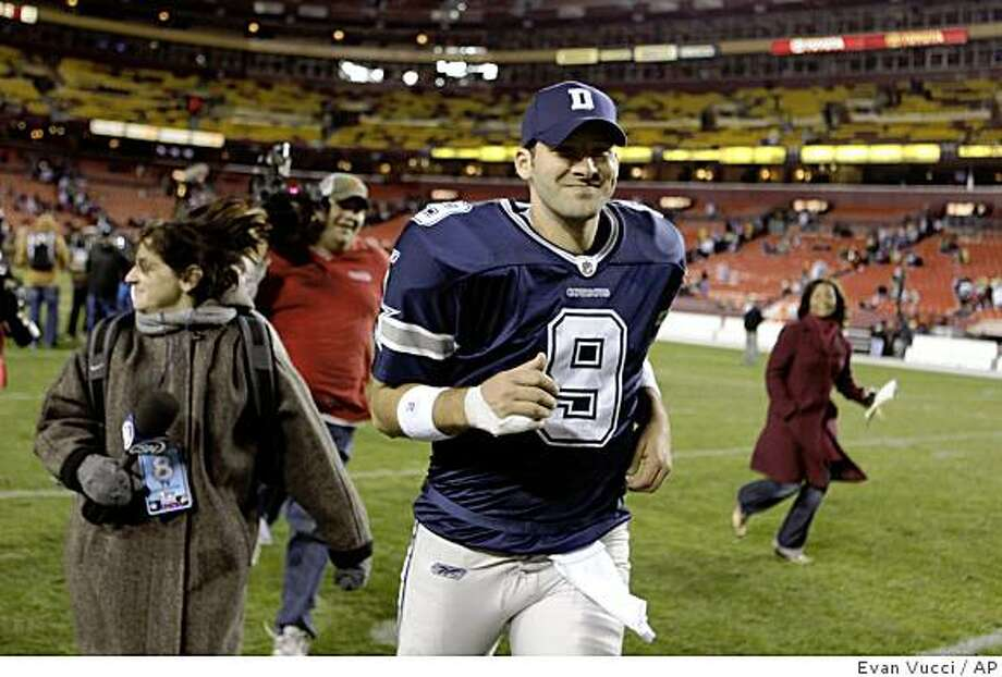 Reporters chase Dallas Cowboys quarterback Tony Romo off the field after he led his team to a 14-10 victory over the Washington Redskins on Sunday, November 16, 2008 in Landover, Md.  (AP Photo/Evan Vucci) Photo: Evan Vucci, AP