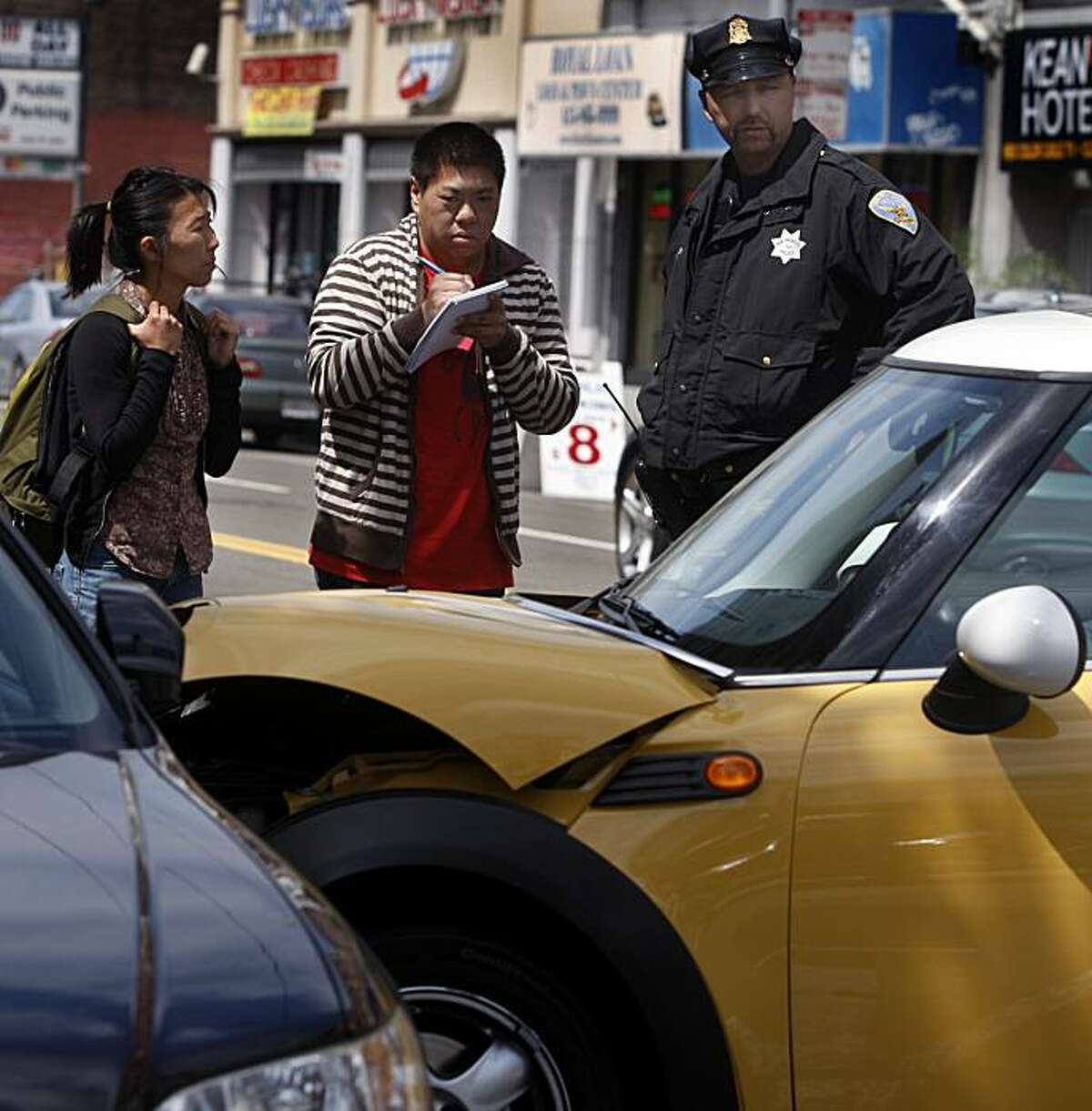 Monica Jensen and Jerold Chinn interview a police officer while covering a traffic accident for the San Francisco Public Press newspaper in San Francisco, Calif., on Friday, June 18, 2010. The small start-up news operation publishes its first print edition on Tuesday, June 22.