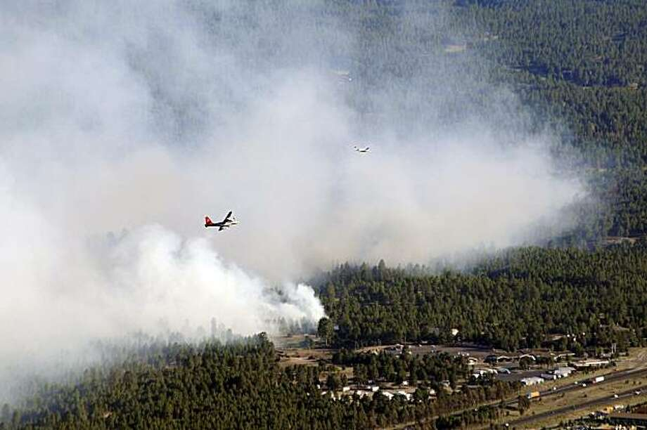 In this June 19, 2010 photo provided by Kelly Hibbs, an aircraft flies over a wildfire in Flagstaff, Ariz, as seen from Mount Elden.  Firefighters are bracing for windy conditions Sunday as they battle a 350-acre wildfire burning near downtown Flagstaff that prompted evacuations of homes and a hotel. Fire officials say the wind is expected to reach 30 mph around midday. (AP Photo/Kelly Hibbs) MANDATORY CREDIT; NO SALES Photo: Kelly Hibbs, AP