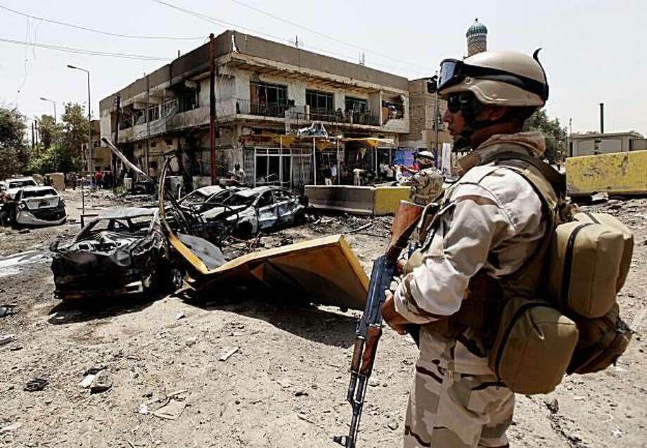 An Iraqi Army soldier stands guard at the site of a car bomb attack in Baghdad, Iraq, Sunday, June 20, 2010. Twin car bombs exploded Sunday near a major square in Baghdad, killing several people and wounding dozens in the latest attack targeting a high-profile area in the capital. Photo: Hadi Mizban, AP