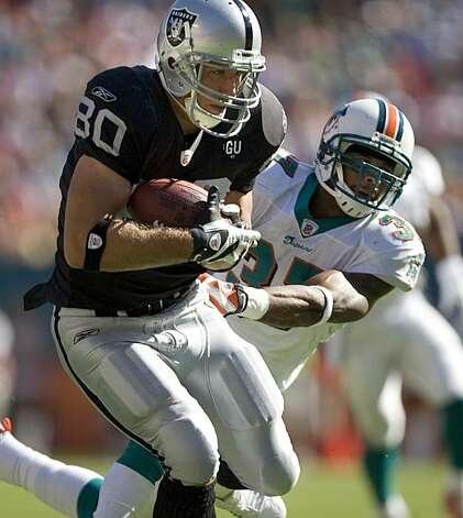 Raiders tight end Zach Miller is subdued by Dolphins safety Yeremiah Bell in the third quarter  as the Miami Dolphins beat the Oakland Raiders 15-17 at Dolphins Stadium in Miami, Fla., on Sunday, Nov. 16, 2008. Photo: Kim Komenich, The Chronicle