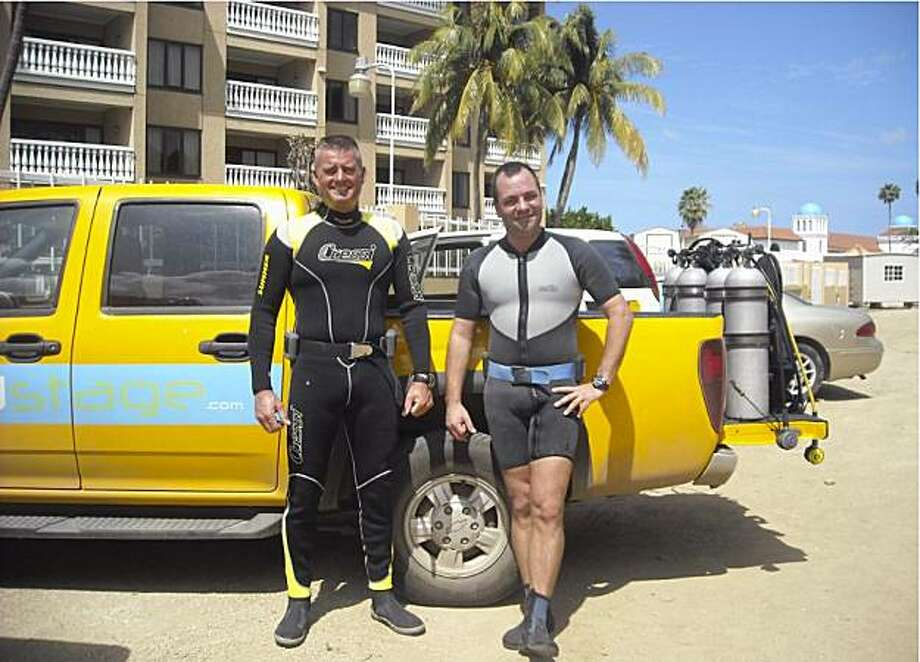 In this Nov. 11, 2009 photo provided by Dick de Bruin, was taken with his camera and shows de Bruin, left, and Toine van der Klooster, both members of  the Royal Dutch Navy, preparing to scuba dive as part of a dive team that was salvaging an anchor fromthe USS Powell for a World War II memorial in Aruba. De Bruin's camera floated away from him during the dive and was found months latter in Key West, Fla. Photo: AP