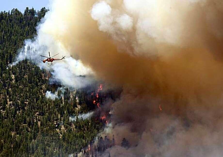 The Schultz Fire burns behind homes along Monday, June 21, 2010 in Flagstaff, Ariz. More than 300 firefighters are battling the Northern Arizona blaze. Photo: Matt York, AP