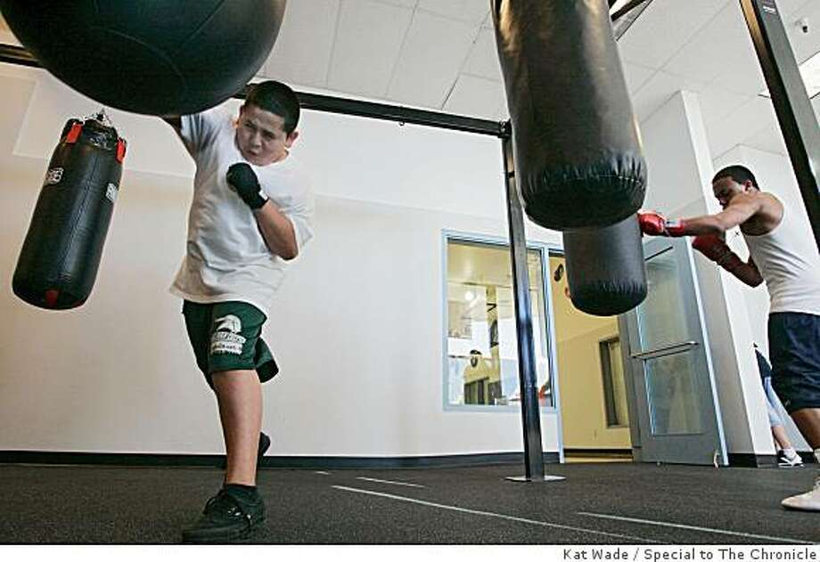 "Sergio Rodriguez, 13, left, and Donovan ""Puerto Rico"" Cardenas, 17, hit punching bags to warm up for boxing class at the P.A.L. Matt Garcia Youth Center in Fairfield, Calif. on Saturday, November 15, 2008. Photo: Kat Wade, Special To The Chronicle"