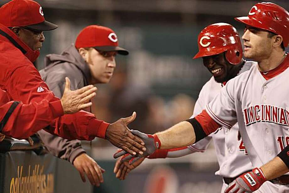 Cincinnati Reds manager Dusty Baker, left, congratulates Joey Votto, right, after Votto hit a two run home run against the Oakland Athletics during the tenth inning of a baseball game Monday, June 21, 2010, in Oakland, Calif. Photo: Ben Margot, AP