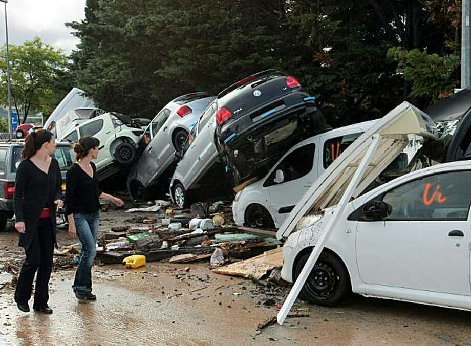 People walk by damaged cars in the aftermath of flooding in a western district of the French south eastern city of Draguignan on June 16, 2010. At least eleben people have been killed by flash floods in Draguignan and in the neighboring city of Luc, caused by heavy rains. TOPSHOTS Photo: Stephane Danna, AFP/Getty Images