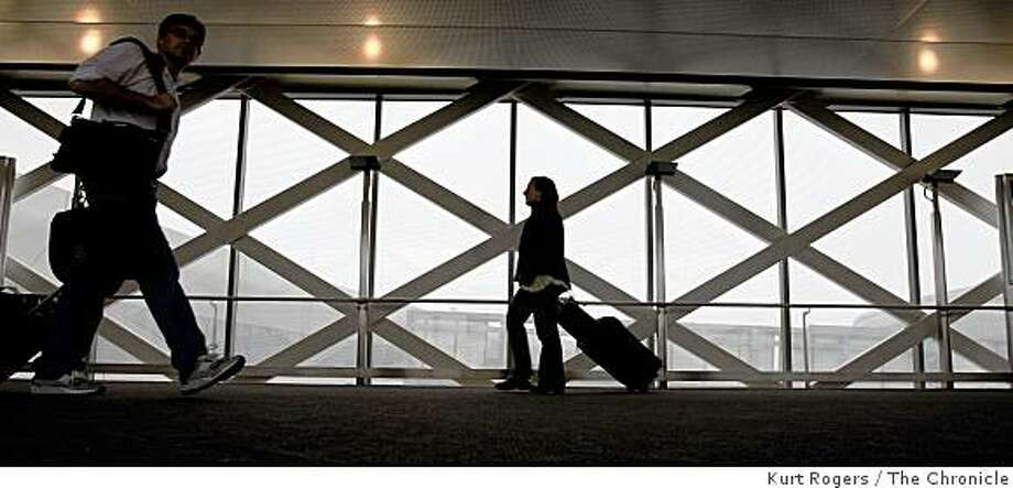 Airline passengers take the walkway between the short-term parking lot and the United Airlines terminal at San Francisco International Airport in San Francisco, Calif., on Nov. 19, 2008. Photo: Kurt Rogers, The Chronicle