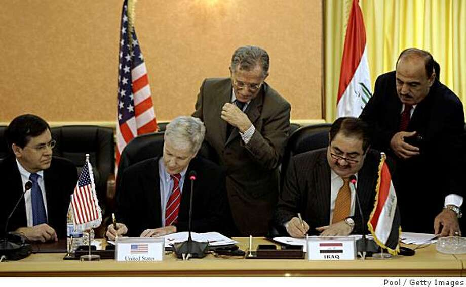 BAGHDAD, IRAQ - NOVEMBER 17:  Aides to U.S. Ambassador to Iraq, Ryan Crocker, second from left, and Iraqi Foreign Minister Hoshyar Zebari, second from right, are on hand during a signing ceremony for a security pact on November 17, 2008 in Baghdad, Iraq. The security pact will let U.S. troops stay in Iraq until 2011 after it was approved by the cabinet at the Iraqi Foreign Ministry. The pact must still be approved by the Iraqi parliament, but Foreign Minister Hoshiyar Zebari said he expected this to happen by the end of the month. (Photo by Khalid Mohammed - Pool/Getty Images) Photo: Pool, Getty Images