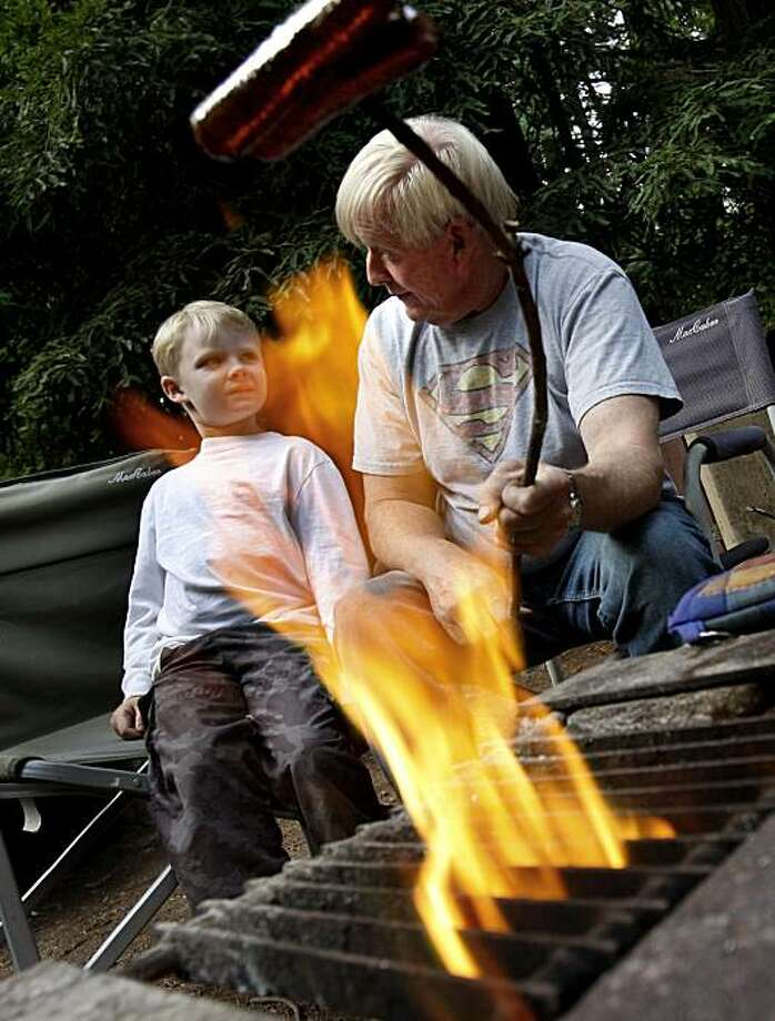 Andrew Dulaney, left, and his father Ron, from Ceres, Calif. cook dinner (hotdogs) over a fire at their campsite at Samuel P Taylor ParkMany Northern California campers may soon have to do without the traditional campfire, but at Samuel P. Taylor Park in Marin County campfires are still permitted. Many federal and state parks are ending campfires in an attempt to prevent wildfires.  Photo by Brant Ward / The Chronicle Photo: Brant Ward, The Chronicle
