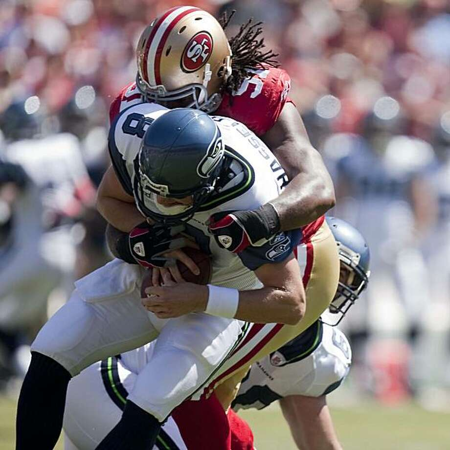 Defensive end Ray McDonald of the San Francisco 49ers sacks quarterback Matt Hasselbeck of Seattle Seahawks during the first quarter at Candlestick Park in San Francisco on Sunday. Photo: Stephen Lam, The Chronicle