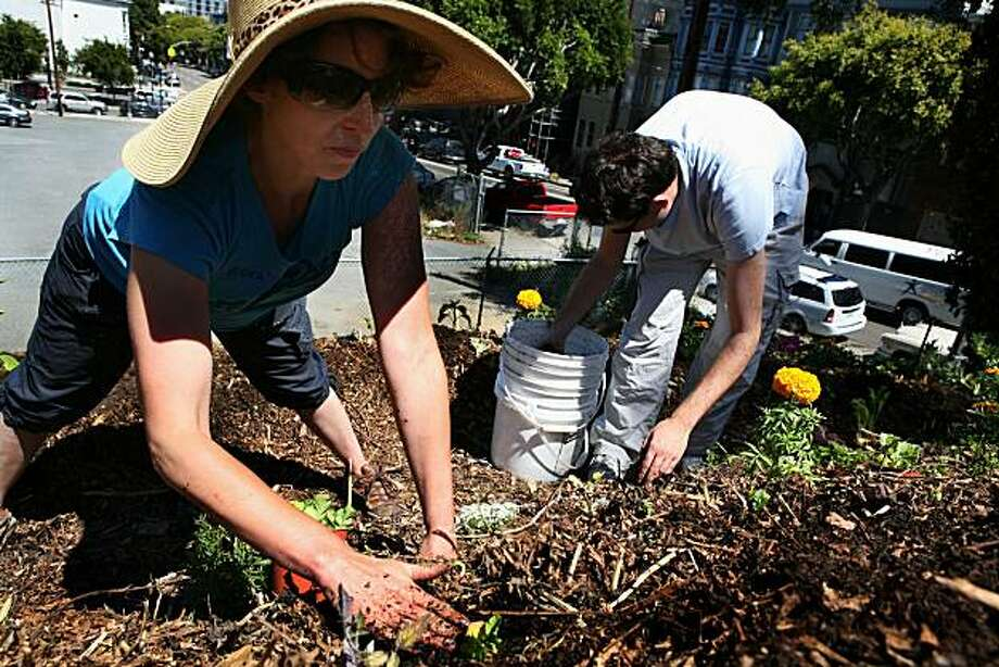 Volunteer Rebecca Alon (left) is transplanting radishes with fellow volunteer Derek Parham in a berm created at the end of the former south bound 101 on-ramp at the Hayes Valley Farm on Sunday, June 13, 2010 in San Francisco, Calif.  The community run farm started in January of 2010 and is located on Laguna between Fell and Oak. Photo: John Sebastian Russo, The Chronicle