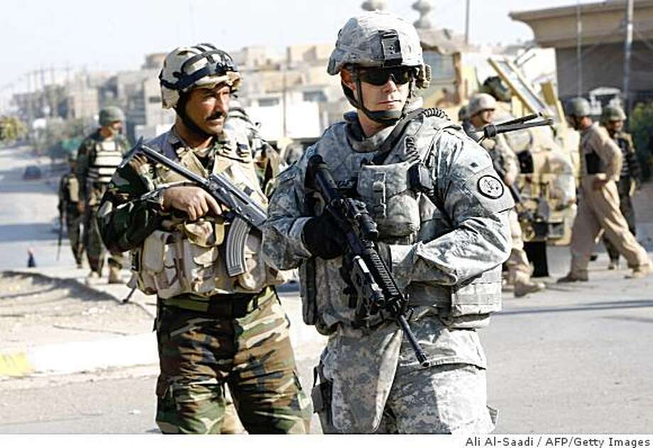 Iraqi and US soldiers gage the area following a road side bomb in the northern city of Mosul, some 370 kms from Baghdad on November 16, 2008. Iraq's cabinet defied fiery opposition from Shiite hardliners today to approve a wide-ranging military pact that includes a timetable for the withdrawal of all US troops by the end of 2011.  AFP PHOTO / ALI AL-SAADI (Photo credit should read ALI AL-SAADI/AFP/Getty Images) Photo: Ali Al-Saadi, AFP/Getty Images
