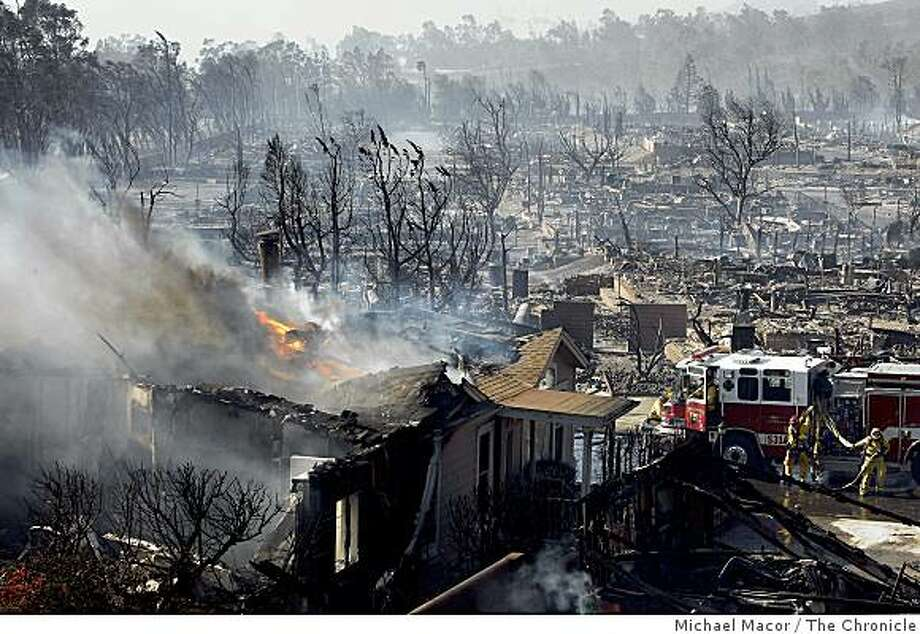 A single family home on the edge of the Oak Ridge trailer park in Sylmar, Calif. continues to burn as firefighters prepare to douse the blaze, on Saturday, Nov. 15, 2008,  after a fast moving fire ripped through the complex destroying most of the homes in the trailer park. Photo: Michael Macor, The Chronicle
