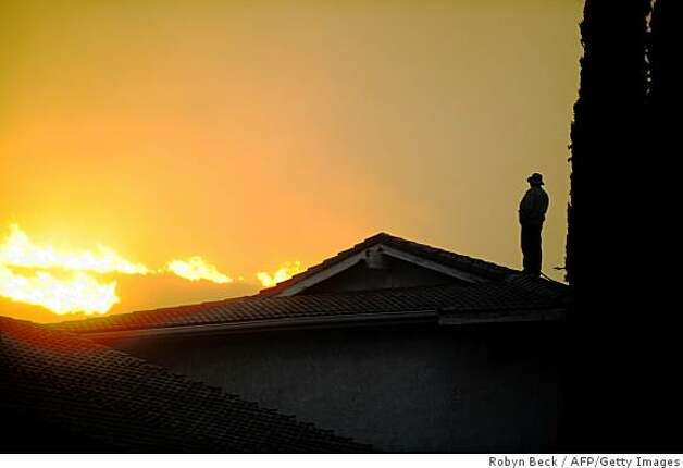 A man watches from the roof of his house as a wildfire burns in the hills behind him, in the Knollwood section of Los Angeles on Nov. 15,  2008. As firefighters tackled the Montecito blaze, a fresh fire erupted near Sylmar in the northern suburbs of Los Angeles late Nov. 14. Photo: Robyn Beck, AFP/Getty Images