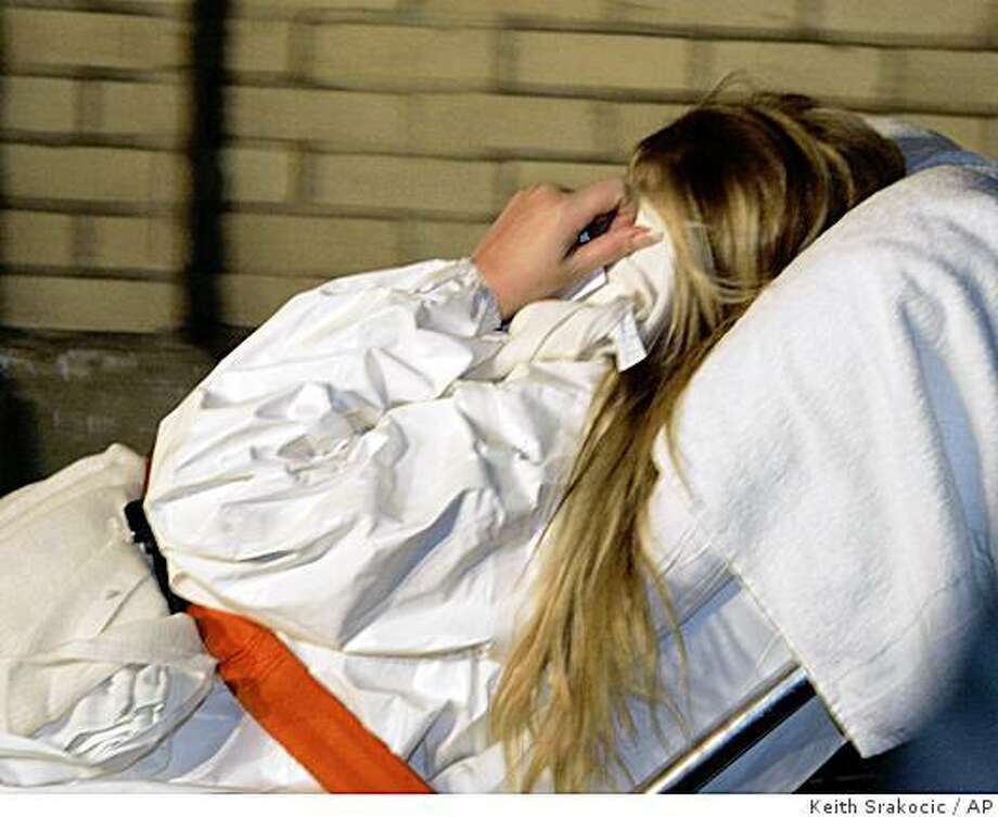 Christina Korbe covers her face as she is taken from the Allegheny County Police headquarters in Pittsburgh, Wednesday, Nov. 19, 2008. Korbe, the wife of drug suspect Robert Korbe  has been charged with killing FBI agent Sam Hicks who showed up at the couple's house near Pittsburgh to arrest her husband Wednesday morning. (AP Photo/Keith Srakocic) Photo: Keith Srakocic, AP