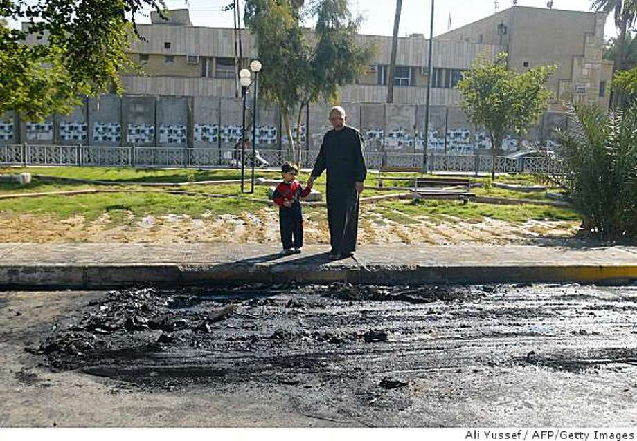 An Iraqi man walk his grandson past the scene of an explosion after a road side bomb detonated as an Iraqi  police convoy drove past in central Baghdad on November 15, 2008. Three police officers and four civilians were wounded in the explosion.  AFP PHOTO / ALI YUSSEF (Photo credit should read ALI YUSSEF/AFP/Getty Images) Photo: Ali Yussef, AFP/Getty Images