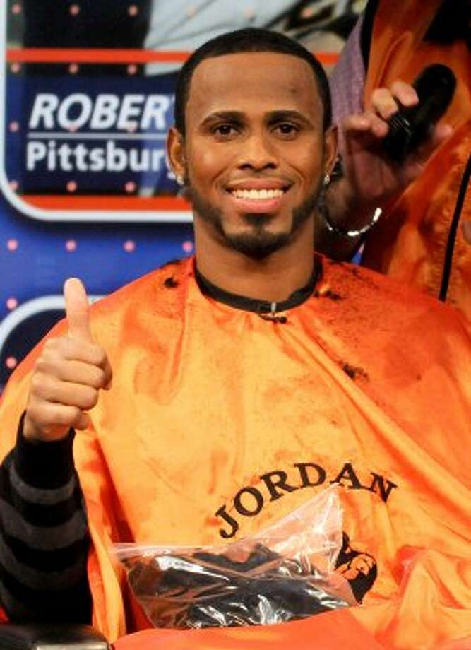In this photo released by MLB Network, Miami Marlins shortstop Jose Reyes reacts after getting a haircut from Jordan of  Jordan's Barber Shop in the Bronx, N.Y.,  at the MLB Network in Secaucus, N.J., Friday, Feb. 3, 2012. Network spokeswoman Lorraine Fisher said the trim will benefit the Make-A-Wish Foundation of Southern Florida, which planned to auction the hair on eBay. (AP Photo/Retna, George Napolitano, via MLB Network) MANDATORY CREDIT (AP)