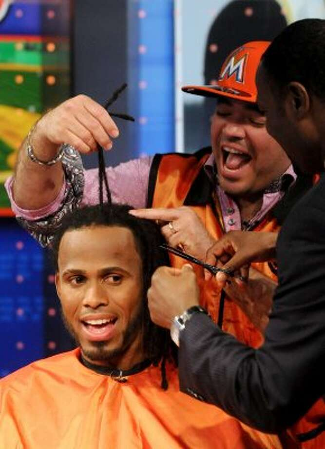 In this photo released by MLB Network, Miami Marlins shortstop Jose Reyes gets a haircut from Jordan of  Jordan's Barber Shop in the Bronx, N.Y., as Harold Reynolds joins in  at the MLB Network in Secaucus, N.J., Friday, Feb. 3, 2012. Network spokeswoman Lorraine Fisher said the trim will benefit the Make-A-Wish Foundation of Southern Florida, which planned to auction the hair on eBay. (AP Photo/Retna, George Napolitano, via MLB Network) MANDATORY CREDIT (AP)