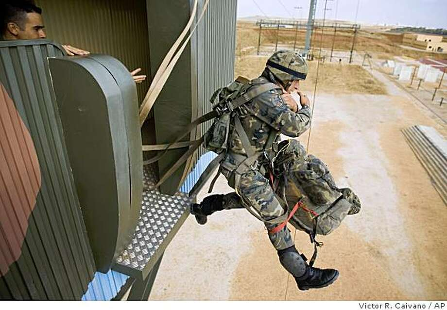 **APN ADVANCE FOR SUNDAY NOV. 16** Spanish soldier Dalton Rafael Jimenez, 22, from Ecuador, jumps off a parachute platform during training at the Parachute Brigade base in Torrejon de Ardoz, in the outskirts of Madrid, on Tuesday, Oct. 14, 2008. Since elimination of the draft in 2002, immigrants from former Spanish colonies, most of Latin American countries and Equatorial Guinea, have been allowed to join the Spanish Armed Forces. Four out of the last 10 soldiers killed in missions abroad were Latin American immigrants.(AP Photo/Victor R. Caivano) Photo: Victor R. Caivano, AP