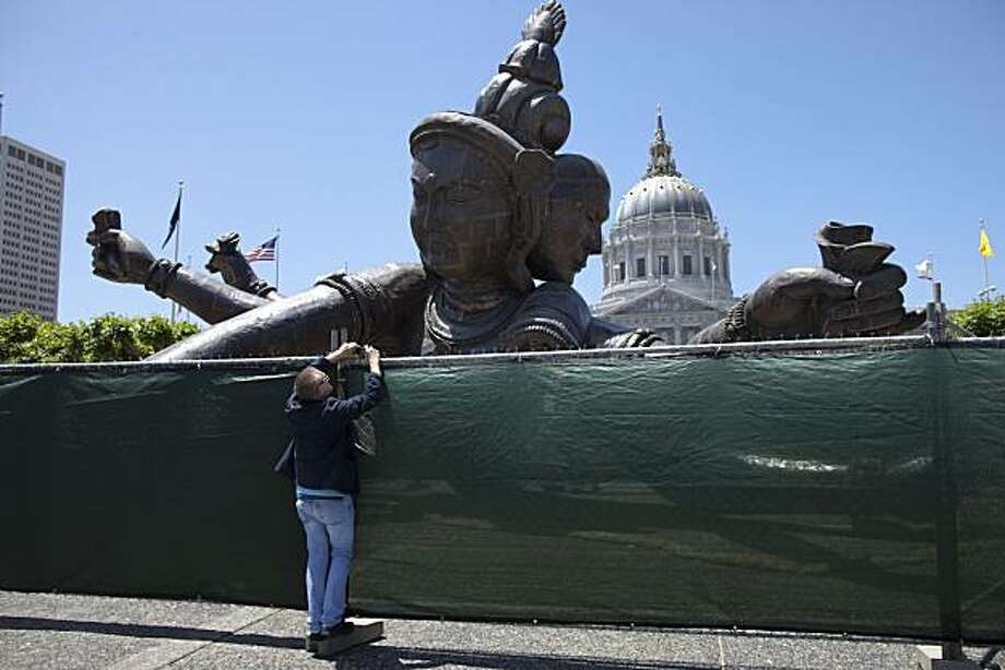"Pat Miller, a city of San Francisco employee takes a photo of the giant ""Three Heads Six Arms Buddha"" sculpture in front of City Hall on June 15, 2010 in San Francisco. Photo: David Paul Morris, Special To The Chronicle"