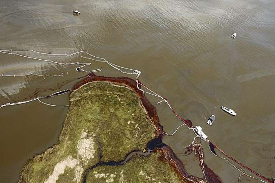 The oil damaged shoreline in the Northern reaches of Barataria Bay is seen amidst work boats in oil polluted waters as Louisiana Gov. Bobby Jindal's tours oil damage in Barataria Bay, La., Thursday, June 17, 2010. Photo: Gerald Herbert, AP