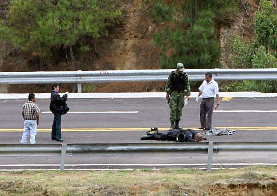 Crime scene investigators and a Mexican army soldier stand over the body of a fallen federal policeman after an ambush on a patrol of federal agents near the town of Zitacuaro, Mexico Monday June 14, 2010. Mexican federal police say 10 of their officers were killed in the attack and several others were wounded. Photo: Agencia MVT-Crisanta Espinosa, AP