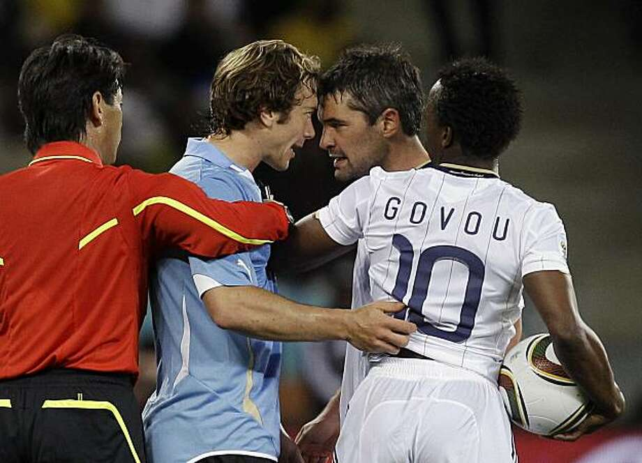 Uruguay's Diego Lugano, left, and France's Jeremy Toulalan, second from right, argue as referee Yuichi Nishimura of Japan, left, and France's Sidney Govou, right, intervene during the World Cup group A soccer match between Uruguay and France in Cape Town,South Africa, on Friday, June 11, 2010. Photo: Julie Jacobson, AP
