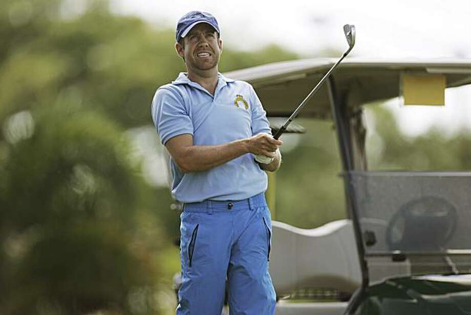 ** ADVANCE FOR WEEKEND, OCT. 18-19** Erik Compton watches his golf ball as he hits practice shots Oct. 9, 2008, in Miami. Compton has had two heart transplants, numerous heart attacka and dodged death dozens of times but is making a run to get onto the PGA Tour. He's also one of a handful of golfers whom the PGA Tour has granted use of a golf cart. (AP Photo/J. Pat Carter) Photo: J. Pat Carter, AP