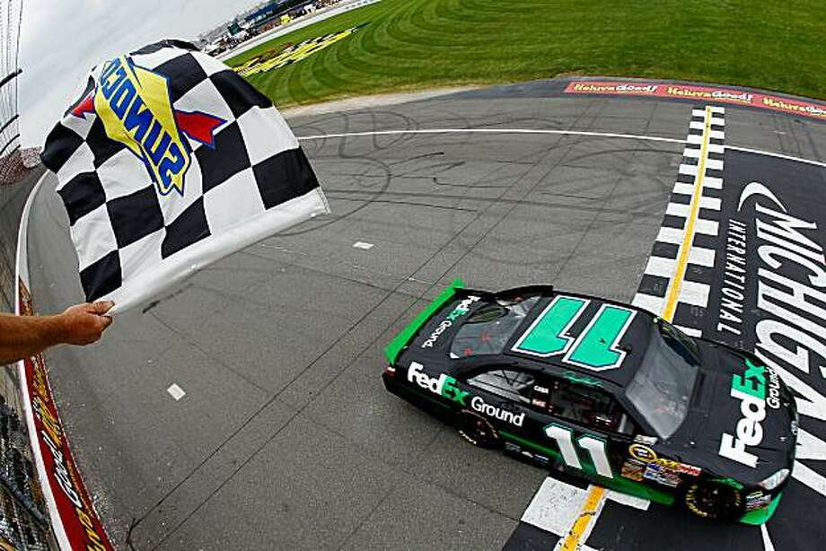 BROOKLYN, MI - JUNE 13:  Denny Hamlin, driver of the #11 FedEx Ground Toyota, crosses the finish line to win the NASCAR Sprint Cup Series Heluva Good! Sour Cream Dips 400 at Michigan International Speedway on June 13, 2010 in Brooklyn, Michigan. Photo: Chris Trotman, Getty Images