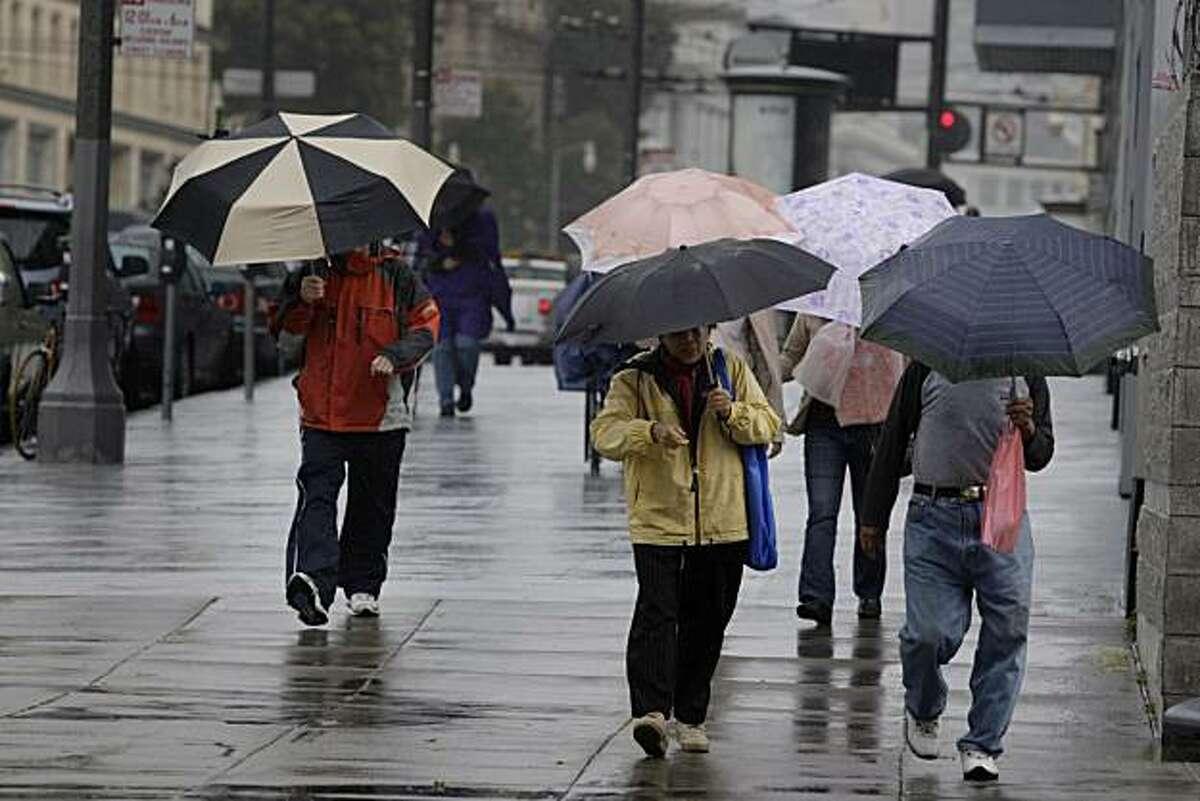 Pedestrians walk underneath their umbrellas in the rain as they walk on Van Ness Avenue in San Francisco, Calif. on Tuesday April 27, 2010.