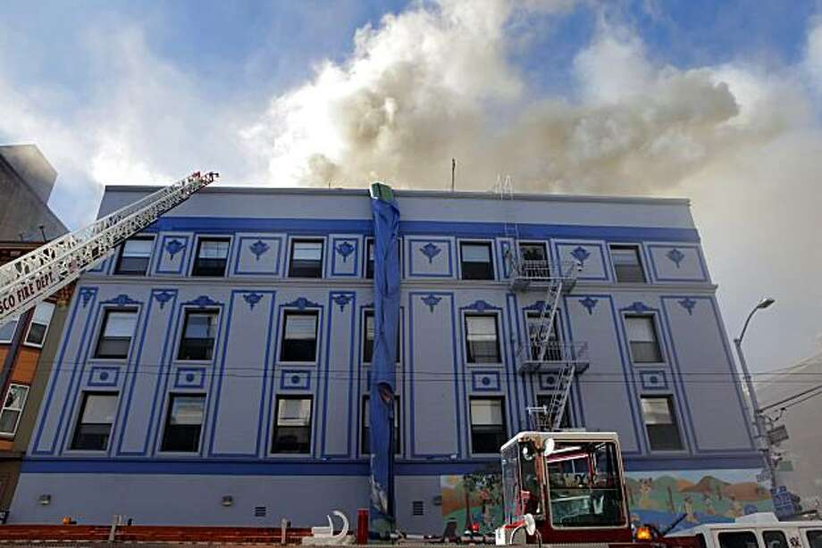 San Francisco firefighters work on a structure fire at 111 Taylor St. on Thursday. The building is a halfway house for parolees. Photo: Carlos Avila Gonzalez, The Chronicle