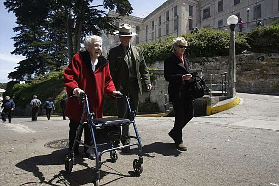 Betty Lou Vickery (l to r) Ranger John Cantwell and Rita Adams (granddaughter in law of Vickery) walk on a road near the cell block on Alcatraz on a recent visit to the island. Betty Lou Vickery lived on Alcatraz when it was an military prison. Photo: Lea Suzuki, The Chronicle