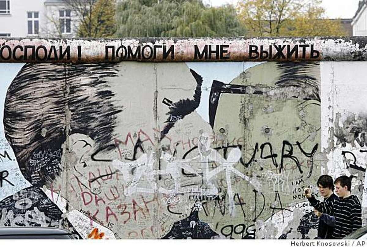 ** FILE ** In this Oct. 15, 2008 file photo, tourists walk past one of the most famous paintings of the East Side Gallery as renovation works start in Berlin, Germany. This brief stretch of the Berlin Wall along the River Spree features famous murals by international artists, and has sadly suffered more recent additions by taggers. (AP Photo/Herbert Knosowski, File)