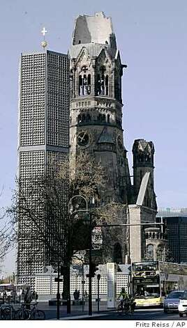 ** FILE ** In this April 13, 2007 file photo, the tower of the famous Kaiser-Wilhelm-Gedaechtnis-Kirche is seen in Berlin. The bombed-out church makes no attempt to hide its scars, the contrast of its decapitated steeple and the serene stained glass of the new chapel are sobering testaments to the city's ongoing struggle to deal with the wounds of WWII. (AP Photo/Fritz Reiss, File) Photo: Fritz Reiss, AP