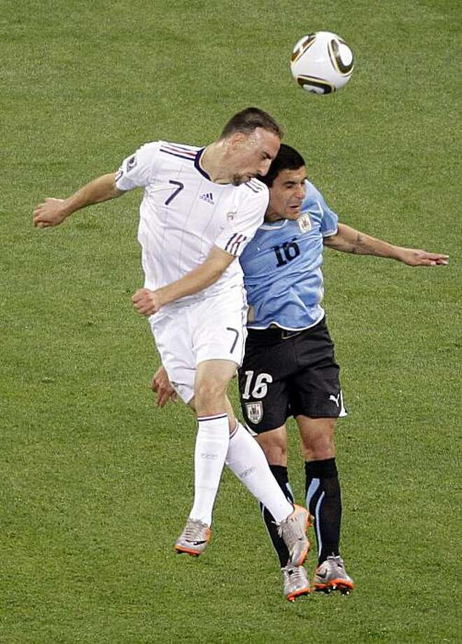 France's Franck Ribery, left, and Uruguay's Maximiliano Pereira jump for the ball during the World Cup group A soccer match between Uruguay and France in Cape Town, South Africa, on Friday, June 11, 2010. Photo: Fernando Vergara, AP
