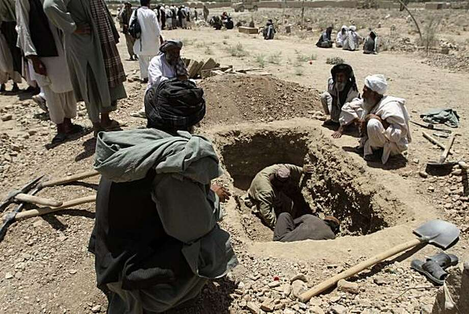 Afghan men burry people killed in a blast in Kandahar's Argandab district Thursday, June 10, 2010.  Scores of people were killed and dozens wounded when a suicide bomb ripped through a wedding party in Kandahar province's Argandab district late Wednesday,officials said. Photo: Allauddin Khan, AP