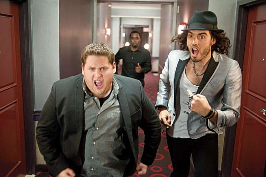 """Aaron (Jonah Hill, left) and Aldous (Russell Brand) run from Aaron's boss, Sergio (Sean Combs, background) in """"Get Him to the Greek,"""" the story of a record company executive with three days to drag an uncooperative rock legend to Hollywood for a comeback concert. The comedy is the latest film from producer Judd Apatow. (Courtesy Glen Wilson/MCT) Photo: Handout, MCT"""