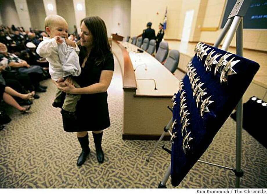 Elizabeth Scheuring holds R.J. Scheuring as they stand near thje officers' stars prior to the ceremonies as the Oakland Police Department swears in 38 new officers at the Elihu Harris State Building in Oakland, Calif., on Friday, Nov. 14, 2008, The department realized its long sought-after goal of fully staffing the force. R.J.'s dad John Scheuring became an officer during the ceremony. Photo: Kim Komenich, The Chronicle