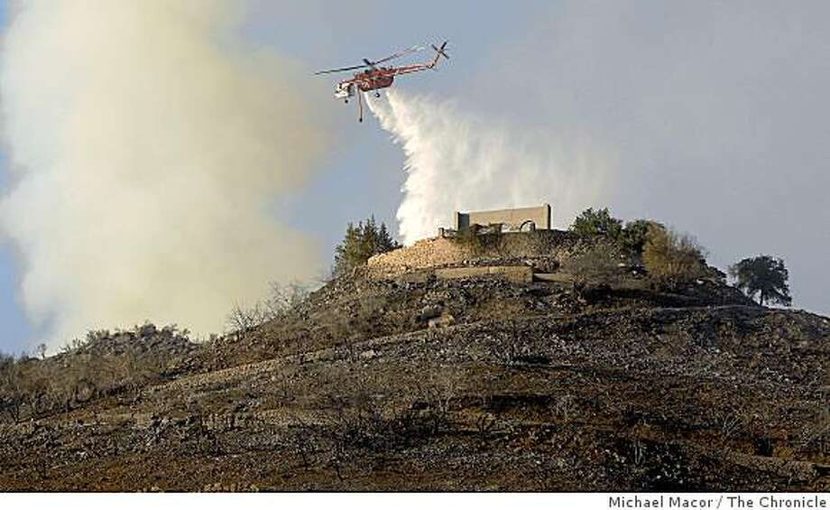 "A helicopter drops water near the Tea House, a historic and defunct tea restaurant in the hills of Montecito. Firefighters continued to douse hot spots of the ""Tea Fire"" on Friday, Nov. 14, 2008 after the fire swept through Montecito, Calif. destroying over 100 homes. Photo: Michael Macor, The Chronicle"