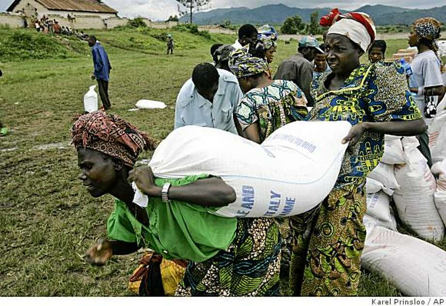 Displaced women receive maize meal from the World Food Program in the town of Rutshuru, 70 kms north of Goma, eastern Congo, Friday, Nov. 14, 2008. The United Nations began distributing food Friday deep in rebel-held territory in eastern Congo, the first large-scale delivery in the area since fighting broke out in late October. (AP Photo/Karel Prinsloo) Photo: Karel Prinsloo, AP